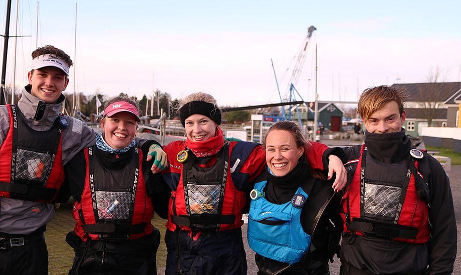 Der var stadig smil på læberne hos sejlerne efter en lang og kold dag på vandet. Fra Venstre: Nikolai Tiedemann, Maria Ravn, Julie Skovbo, Marisa Roch og Sophus Jarvig.  Foto: Rune Cramer.