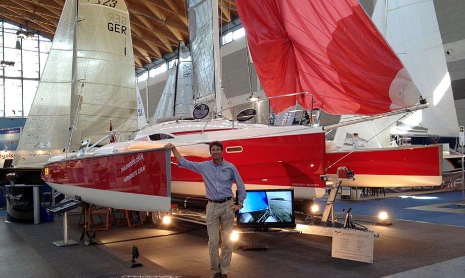 Jens Quorning ser meget lille ud foran en knaldrød Dragonfly 28, på Interboot bådmesse i Frierichshafen. Foto: Quorning Boats