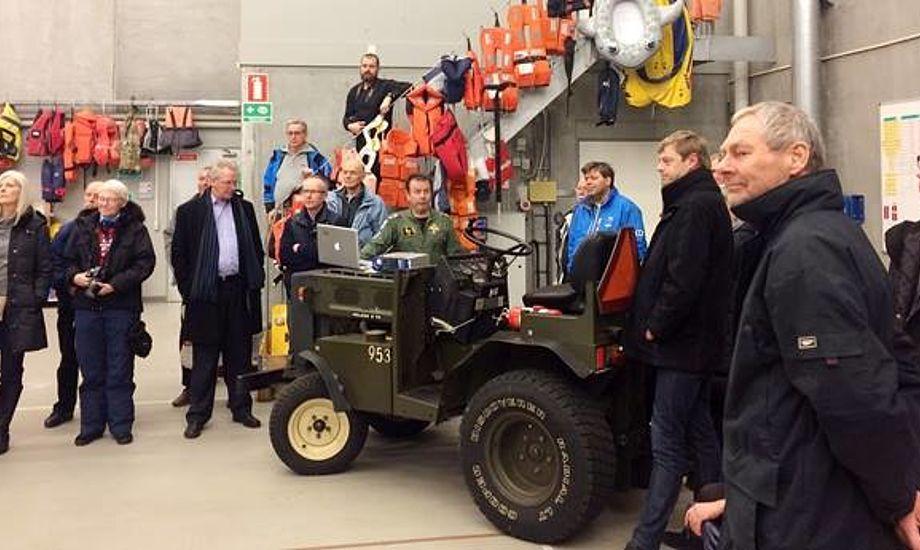 Kursister på besøg hos ESK 722. Traktoren på billedet bruges til at trække helikopteren ud af hangaren. I baggrunden veste og badedyr - alt sammen hentet op i helikopteren under redningsaktioner!