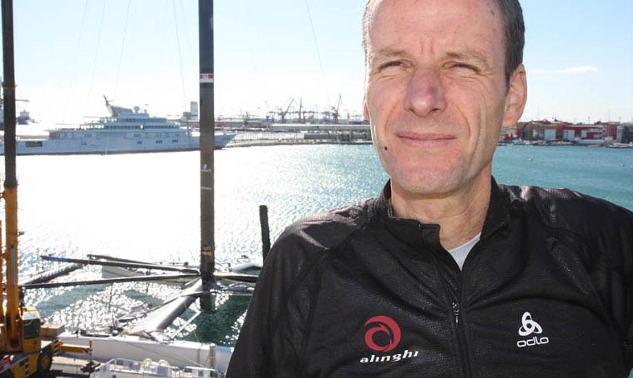 Michael Richelsen med ´Alinghi 5' i baggrunden i Valencia. Katamaranens buede sværd hjælper i øvrigt båden op af vandet. Foto: Troels Lykke