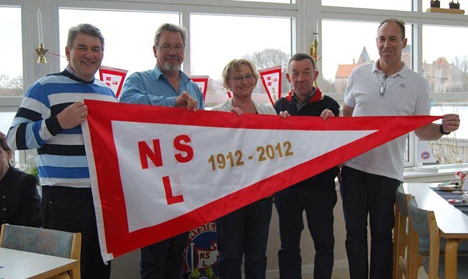 Sejlklubbens bestyrelse med klubstanderen. Foto: Nysted Sejlklub