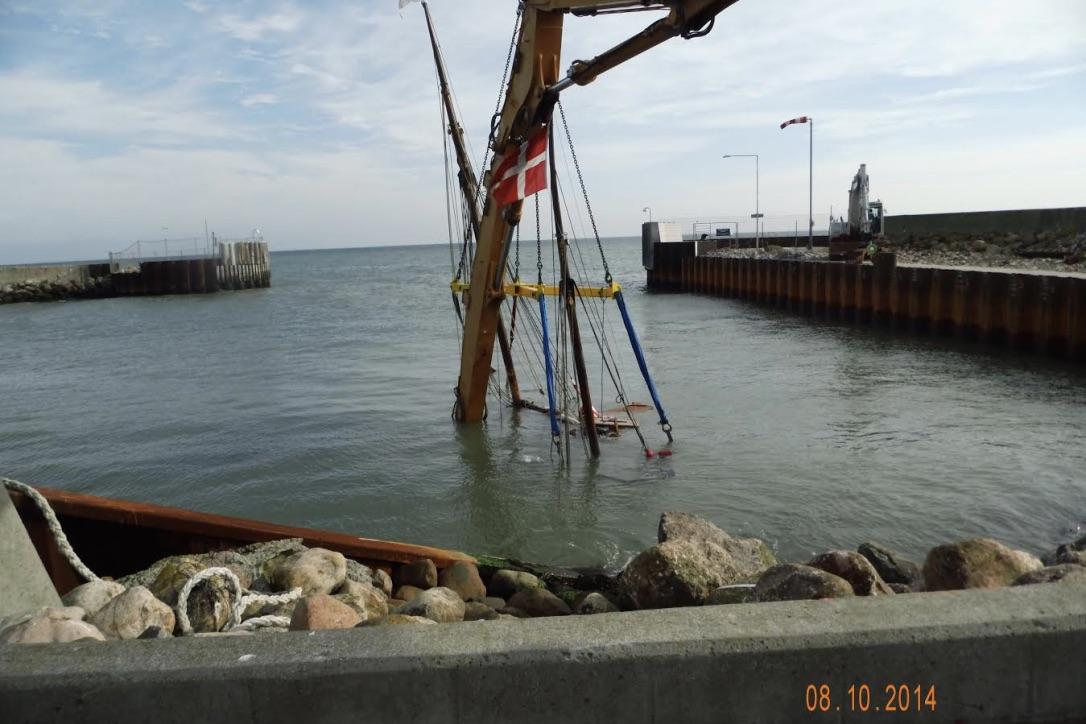 """Efter en mislykket bugsering endte """"Skibet"""" på bunden af Spodsbjerg Havn i 2014. Der gik hul på skroget, da """"Skibet"""" blev slynget af bølgerne mod kajkanten. Foto: Lise Seidelin"""
